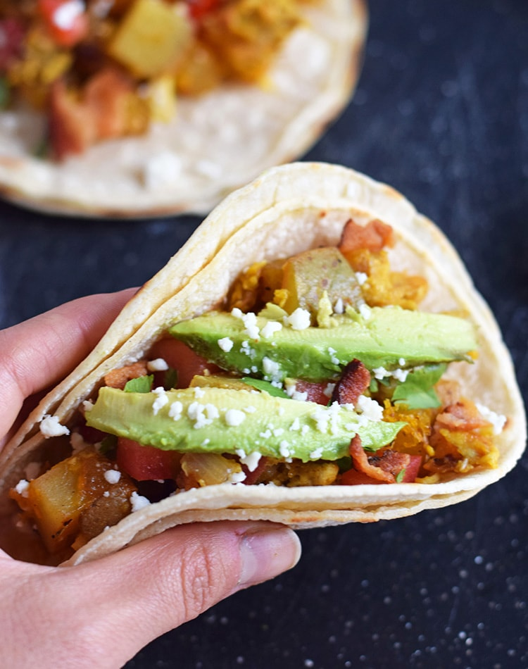 These Sriracha Potato & Egg Breakfast Tacos are the perfect brunch dish that everyone can enjoy. They're Mexican inspired with a little Thai flare. They're easily made vegetarian by omitting the bacon, are gluten free, paleo and pretty freakin' tasty! // isabeleats.com