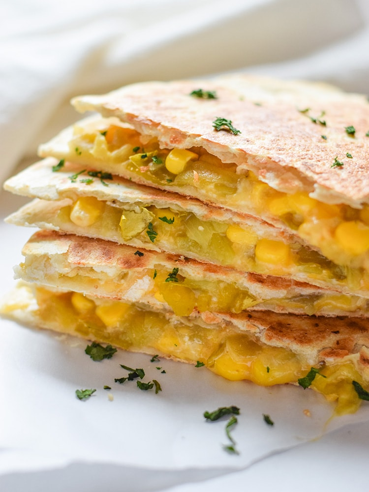 These Easy Green Chile Corn Quesadillas take only 12 minutes to make, are an easy lunch or dinner option and are vegetarian friendly! Plus, they're also an inexpensive meal. All you need are some flour tortillas, canned corn, canned diced green chiles and shredded cheese!