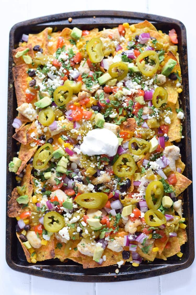 Now you can get your favorite restaurant appetizer right at home! These Easy Loaded Mexican Nachos are topped with all your favorite ingredients and take only 12 minutes to make. Perfect for parties or lazy weekend meals! Is gluten free and can easily be made vegetarian.